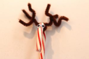 Christmas Craft step 2 glue on google eyes on candy cane reindeer that has brown pipe cleaner antlers