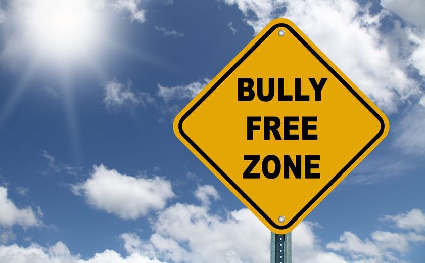 Yellow traffic sign reading bully free zone. Dealing with bullies