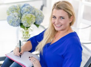 woman in blue shirt writing in journal as part of morning routine