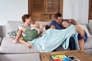 family enjoying family time cuddled on a couch with a blanket