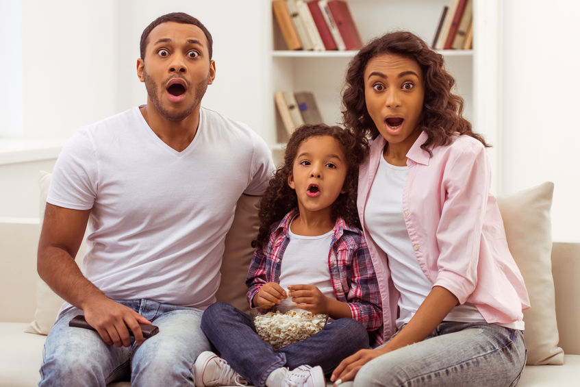 cute little afro-american girl and her beautiful young parents looking at camera and showing surprise while sitting on a sofa make family time together while watching tv