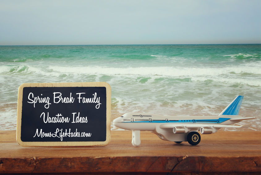 Spring Break Family Vacation Ideas on chalk board on beach with a toy plane