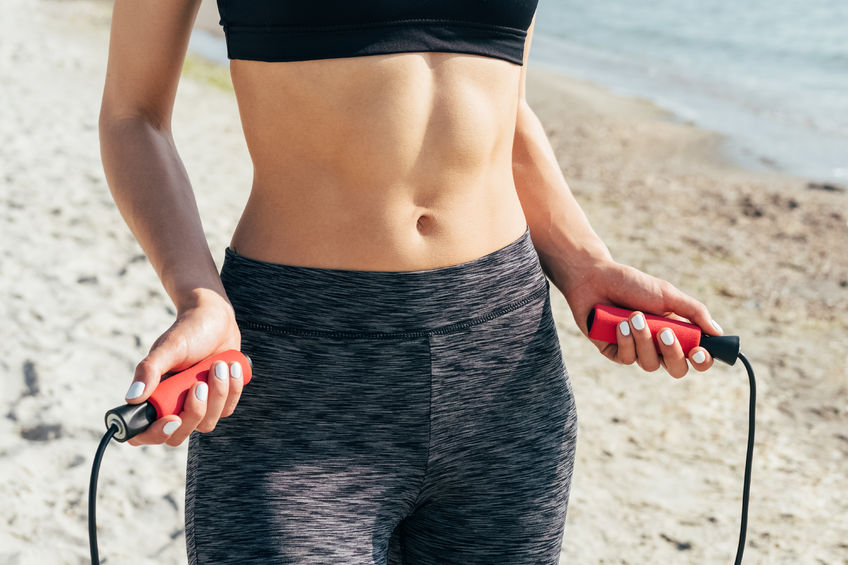 close-up of a girl with a flat stomach with a skipping rope in her hands on the beach