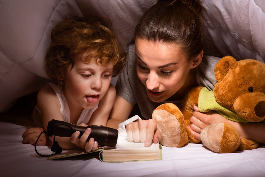 young modern mother reading bedtime stories for kids to her son using a flashlight in a hut of blankets