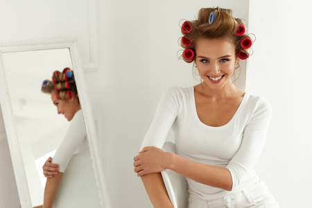 Woman wearing a white shirt getting ready for a night out. She followed her date night beauty tips and her hair is in rollers