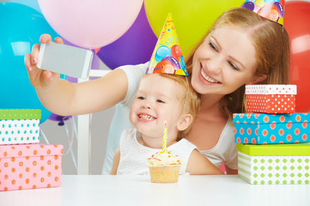Happy mom and daughter taking a selfie at a birthday party on a budget