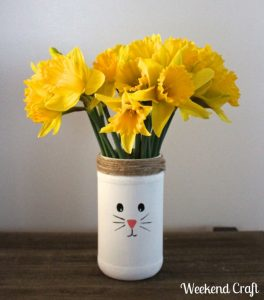 A white vase with a bunny face made as easter craft for kids with yellow flowers inside