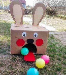 A cardboard box turned into a bunny as a easter craft for kids; multiple colored plastic balls