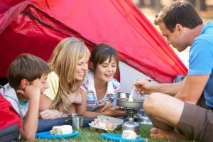 mother father with two children daughter and son having summer camp at home in a tent with dad cooking food