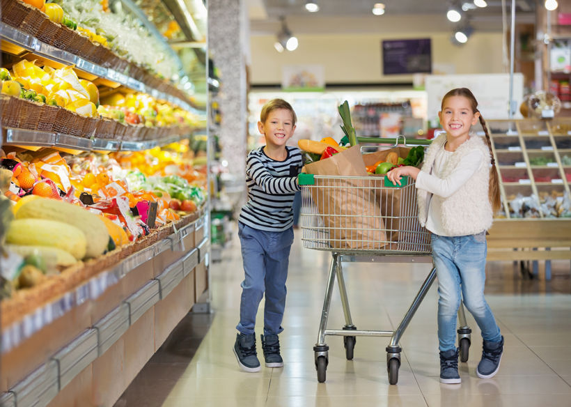 Bother and sister in grocery store produce isle mom is using tips for shopping with kids