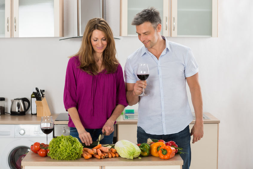 Wife cooking to make her husband feel special; they both have a glass of wine; wife is cutting vegetables