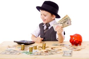 little boy in black hat and tie at the table counts money, isolated on white showing you how to teach kids to budget