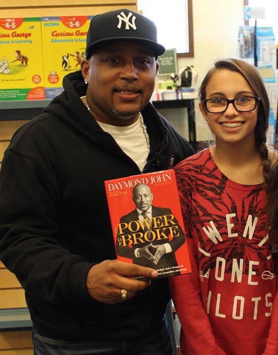 Daymond John with young girl holding a copy of his book teaching entrepreneurial kids