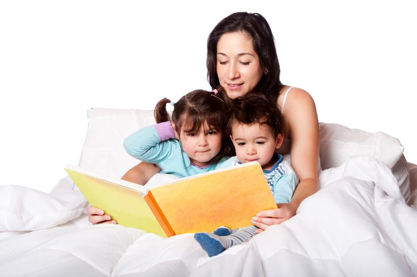 mother reading short bedtime stories to daughter and son kids in bed, isolated.
