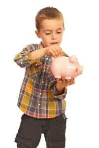 Little boy showing you how to teach kids to budget by putting a coin in a pink piggy bank; white background