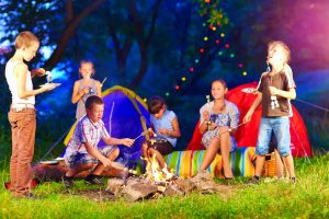 choosing a summer camp kids around a bonfire making s'mores tents and string lights behind them