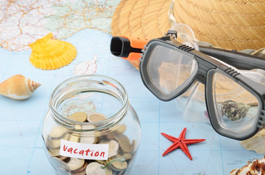 jar with coins in it and a snorkel mask on top of a map for how to vacation on a budget