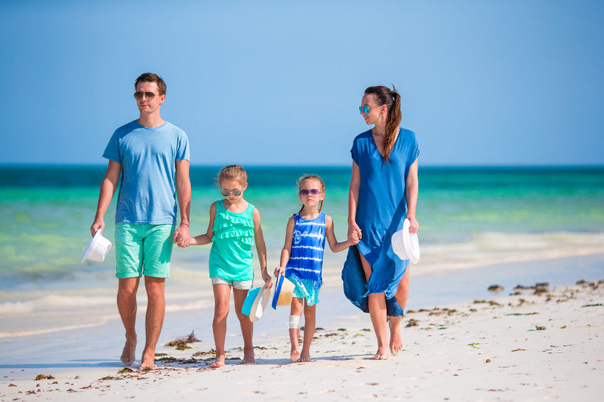 US locations for family vacation two parents and two children walking on a beach holding hands