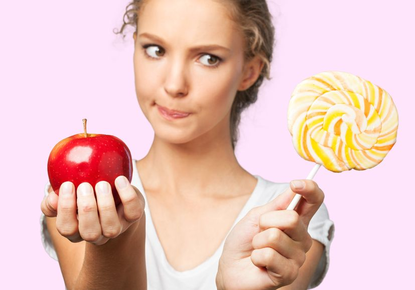 young blonde girl holding an apple and a lollipop type 2 diabetes prevention