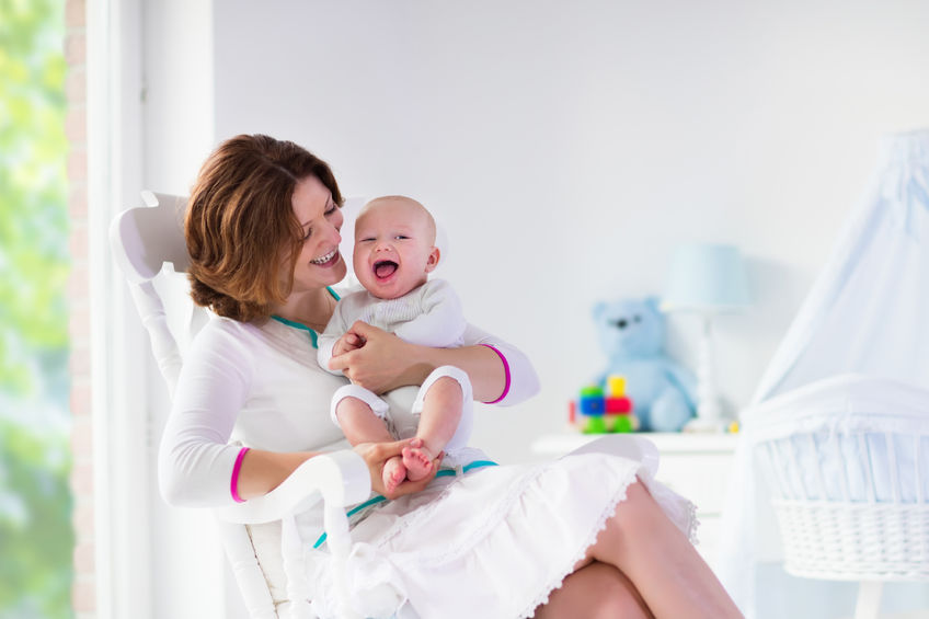 tips for new moms young mother dressed in white holding her newborn baby laughing on her lap while sitting in a rocking chair