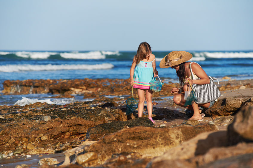 mom and daughter vacation ideas at the beach together on the rocks