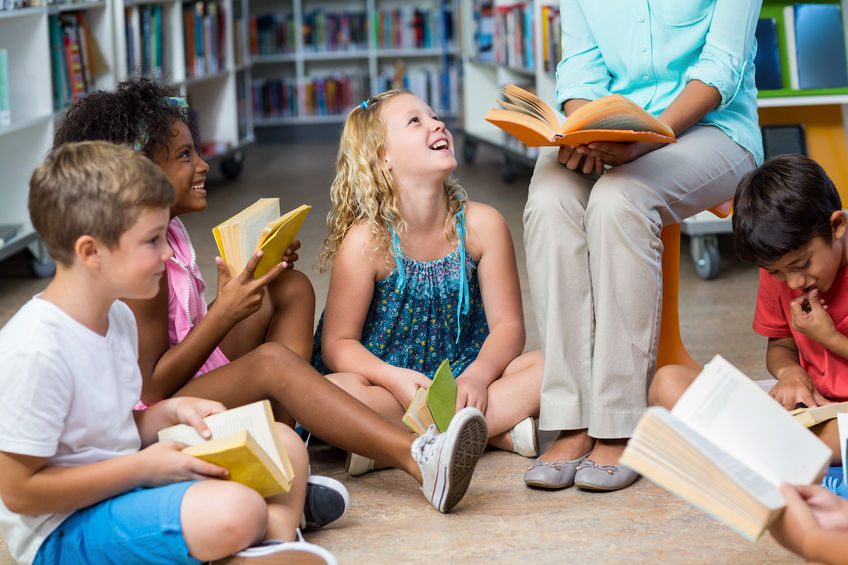 save money as a stay at home mom library activity female teacher with smiling children reading books in library sitting in a circle on the floor